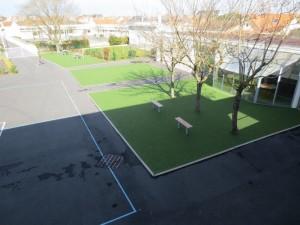 Vue d'une partie de la cour de récréation, avec le restaurant scolaire à droite.